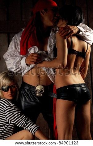 Pirate  with pair Sexy passionate girls against wooden background - stock photo