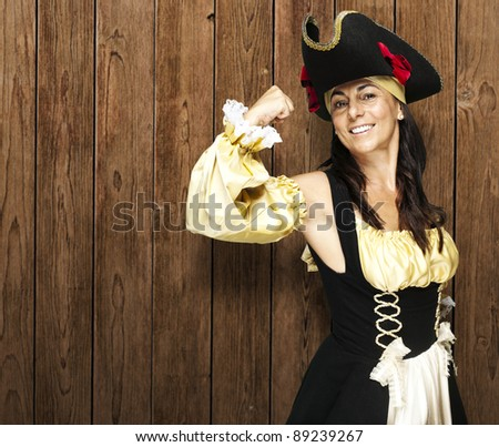 pirate woman gesturing victory against a wooden wall - stock photo