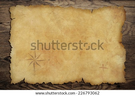 Pirates' old parchment treasure map on wood background - stock photo