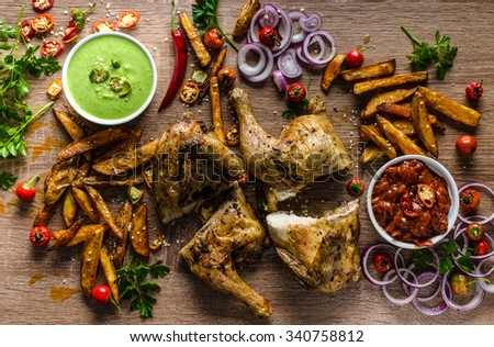 Piri piri spicy chicken with herbs and two spicy sauce, rustic tomato with red pepper and green pepper extra hot - stock photo