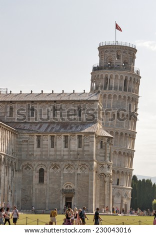 PISA, ITALY - SEPTEMBER 04, 2014: Tourists walk and pose for photography in front of the Duomo Cathedral and Pisa Leaning Tower on Piazza dei Miracoli. This site is the main tourist attraction in Pisa