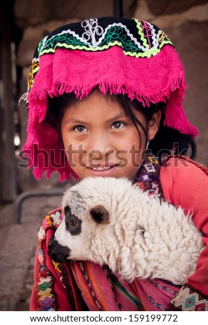 PISAC, PERU - JANUARY 3: Unidentified Quechua girl in traditional clothing with baby llama on January 3, 2010 in Pisac, Peru. The Quechua are a diverse indigenous ethnic group of the Andes. - stock photo