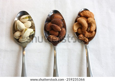 pistachio, almond and cashew nuts decorated on stainless spoons - stock photo