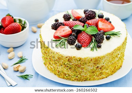 pistachio cake with berry compote and rosemary mousse on a blue background. tinting. selective focus - stock photo