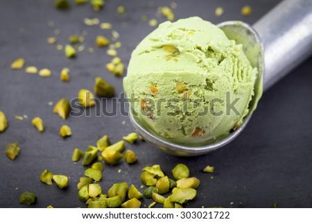 Pistachio ice cream scoop with pistachio nuts on a black stone background. - stock photo