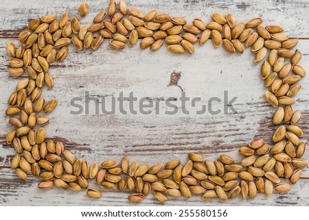 Pistachio nuts aligned on white wooden background with copyspace for text - stock photo