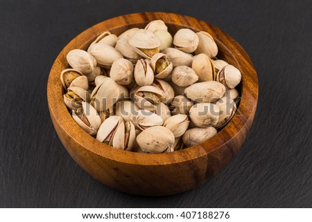 Pistachio nuts in wooden bowl on dark background - stock photo