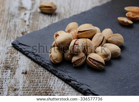 Pistachio nuts on slate board. Selective focus - stock photo