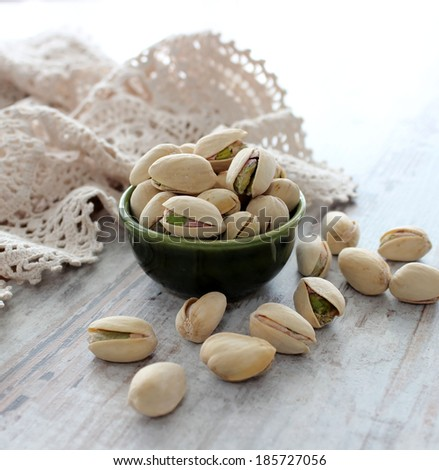 Pistachio nuts on wooden background - stock photo