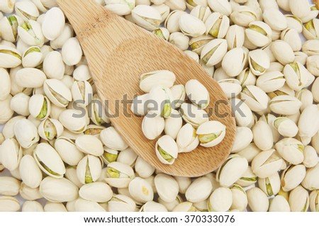 Pistachio nuts with wooden spoon - stock photo