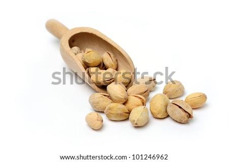 Pistachio on wooden scoop on white background - stock photo