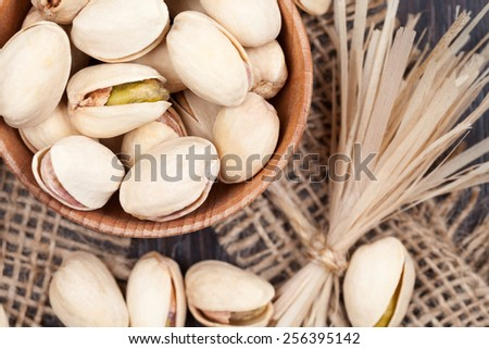 Pistachio superfood mix in a wooden bowl on vintage textile background - stock photo