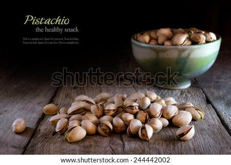 pistachios in a ceramic bowl and some loose nuts on rustic wood, sample text in the dark background, pistachio the healthy snack - stock photo