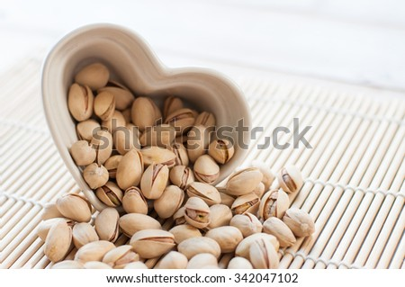 Pistachios in ceramic bowl on wooden table - stock photo