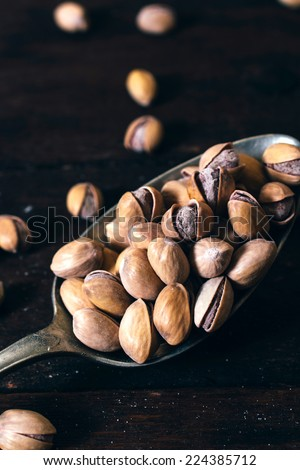 Pistachios in old metal spoon,selective focus  - stock photo