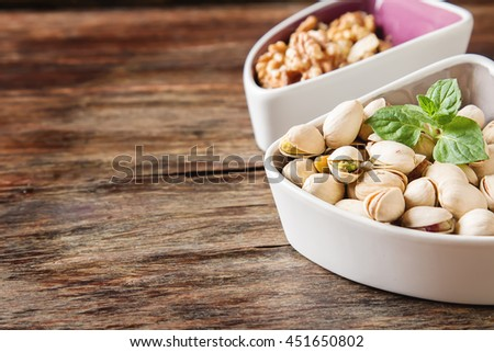 pistachios in the shell and walnuts with a mint on wooden background - stock photo