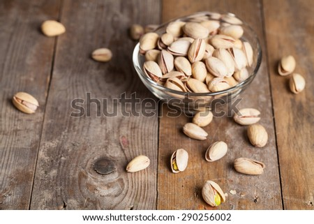 pistachios on wood background - stock photo