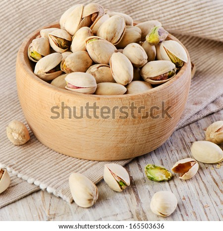 Pistachios on wooden table. Selective focus - stock photo