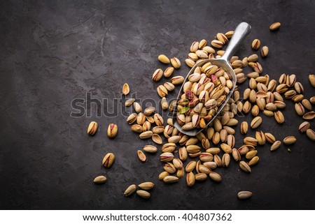 Pistachios over dark background. Food background with copyspace. Top view - stock photo