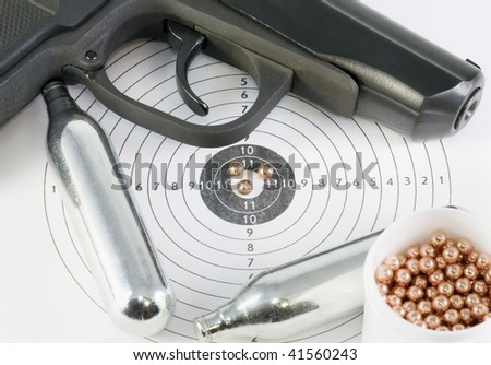 pistol and gas cylinders on the arms of the target - stock photo