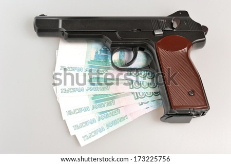 Pistol and money on gray background - stock photo