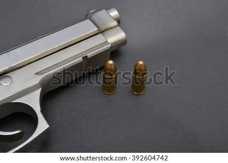 Pistol gun and bullets on black background - stock photo