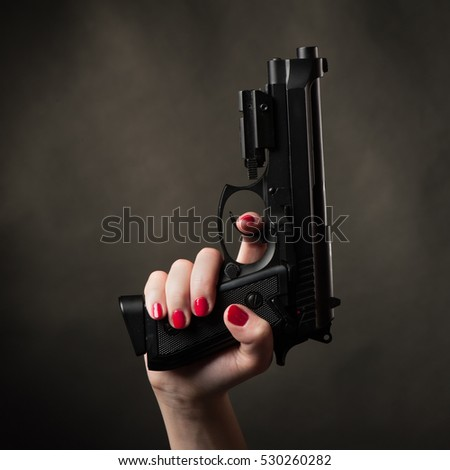Pistol in female arm on black background