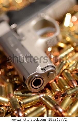 Pistol lying on brass bullets - stock photo