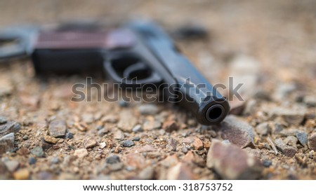 Pistol on ground. Selective focus with super shallow depth of field. - stock photo