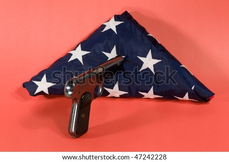pistol pointed at a folded american flag - stock photo