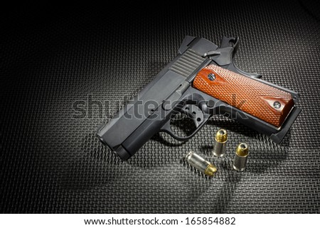 Pistol that is brightly lit with a dark background and sides - stock photo