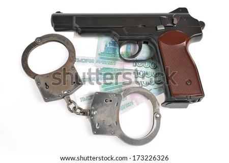 Pistol with handcuffs on money isolated on white background - stock photo