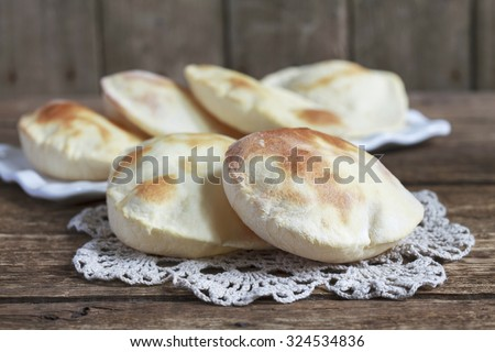 Pita bread on an old wooden table. Rustic style and selective focus. - stock photo