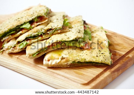 Pita bread with ham and fresh vegetables on the cutting board isolated on white