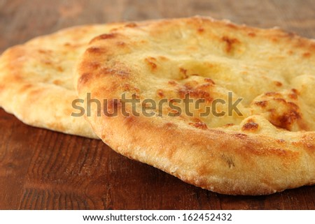 Pita breads on wooden background