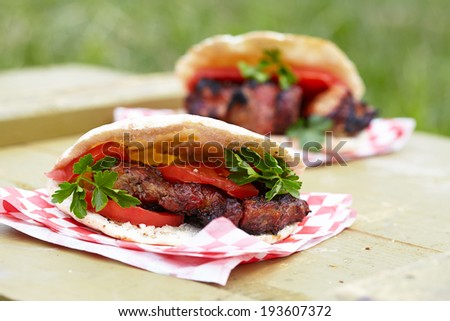 Pita sandwich with grilled meat, tomato and herbs - stock photo