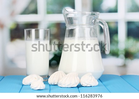 Pitcher and glass of milk with meringues on wooden table on window background - stock photo
