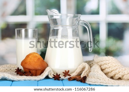Pitcher and glass of milk with muffins on crewnecks knitwear on wooden table on window background - stock photo