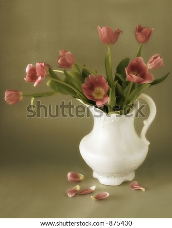 Pitcher and Petals: An antique pitcher of tulips. Great depiction of spring, Mother's Day, vintage representation, etc. - stock photo