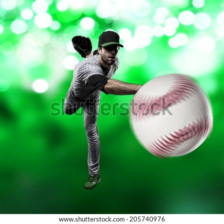 Pitcher Baseball Player on a Green Uniform on Green lights background.