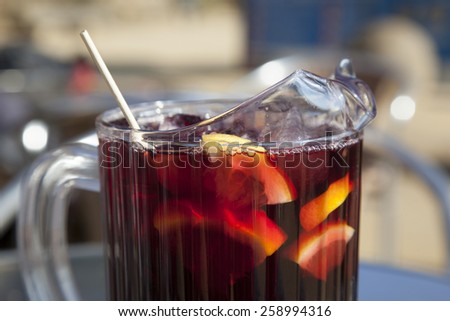 pitcher of cold sangria under the hot sun, red wine with fruit pieces and ice cubes, Spain - stock photo