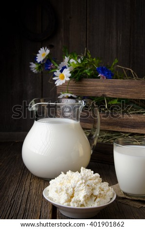 Pitcher of rural milk and glass of milk and white bowl of cottage cheese on a wooden rustic table - stock photo