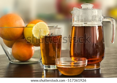 Pitcher with cup of hot black tea with bowl of honey and fruits on kitchen background.