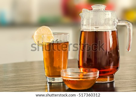 Pitcher with glass of hot black tea with bowl of honey on kitchen background.