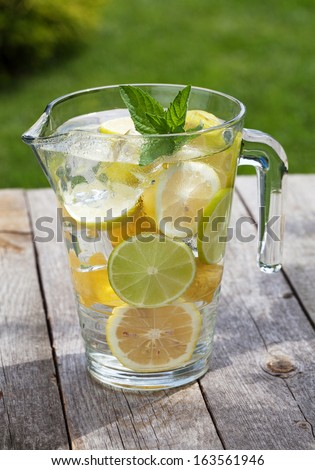 Pitcher with homemade lemonade on wooden table - stock photo