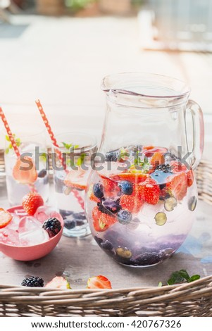 Pitcher with water, berries and  ice cubes on table over garden terrace background. Home scene with summer drinks. - stock photo