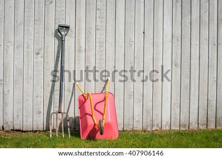 Pitchfork and a wheelbarrow at a fence in a garden - stock photo