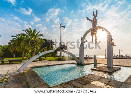 "PITSUNDA, ABKHAZIA, SEPTEMBER 23, 2017: Famous sculptural composition ""The Sea"", which depicts pearl divers and dolphins, in  Pitsunda in the rays of the rising sun in the central beach."