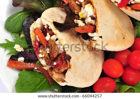 Pitta bread on salad leaves filled with a chicken - stock photo