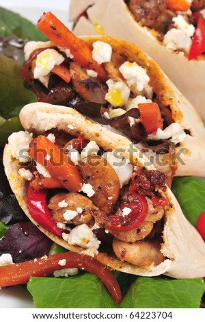 Pitta bread on salad leaves filled with a chicken, vegetables and feta cheese - stock photo